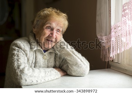 Elderly woman sits at a table near the window.