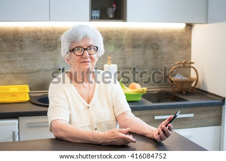 Elderly woman sitting at table and using a smartphone.