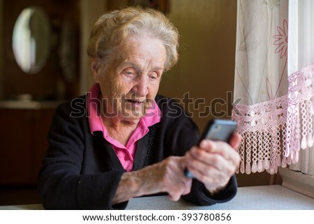 Elderly woman sitting at table typing on a smartphone. - stock photo