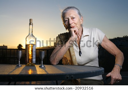 Elderly woman sitting at the table with bottle of white wine outdoors at sunset. - stock photo