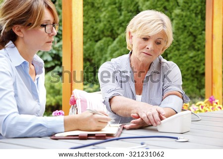Elderly woman sitting in the garden with home health care nurse an using blood pressure.  - stock photo