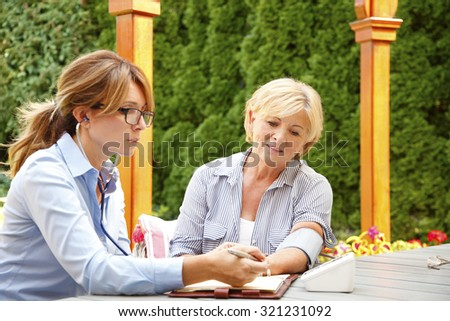 Elderly woman sitting in the garden with home health care nurse an using blood pressure. Home caregiver female consulting with her patient.  - stock photo