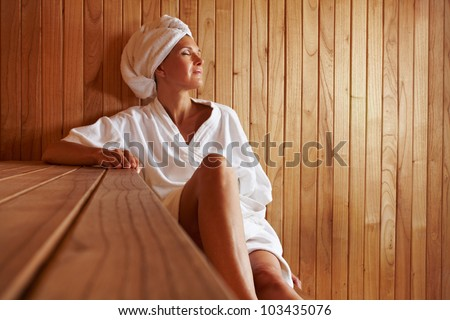 Elderly woman sitting relaxed in a wooden sauna - stock photo