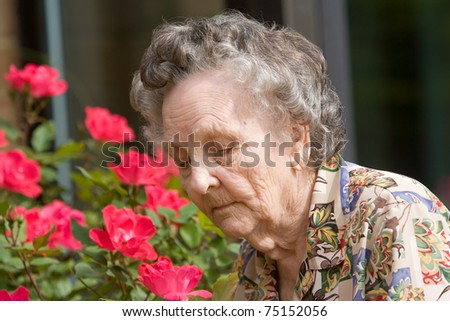 Elderly woman smelling flowers outdoors during springtime - stock photo