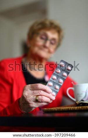elderly woman staring at her pills/ medicine/ elderly woman looking at her medication - stock photo