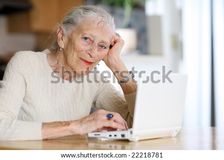Elderly woman typing on ultra portable laptop computer. Shallow DOF. - stock photo