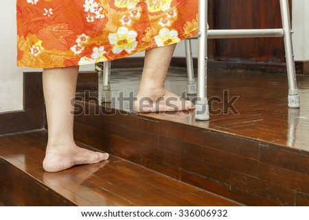 Elderly woman up stairs with walker at home.