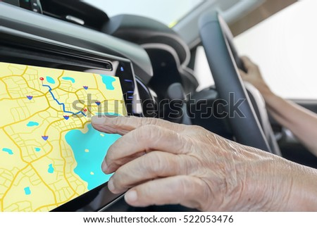 Elderly woman using GPS navigation system in car