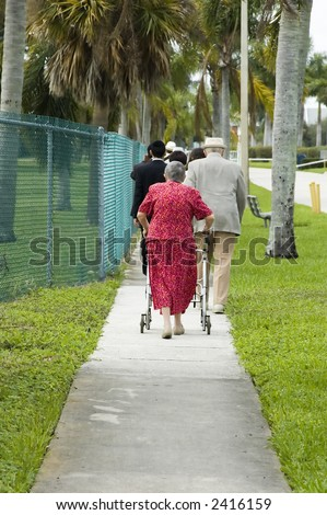 elderly woman walking down a path holding onto a walker - stock photo