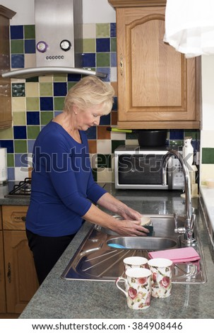 Elderly woman washing up at the kitchen sink