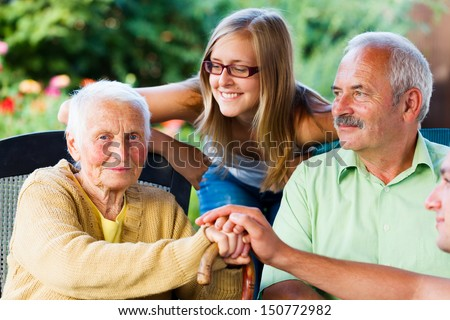 Elderly woman welcoming her family - son and granddaughter in the garden of the nursing home. - stock photo
