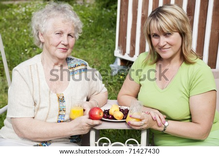elderly woman with adult daughter sitting in the garden and breakfast - stock photo