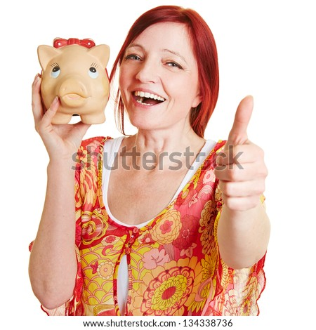 Elderly woman with big piggy bank holding her thumbs up - stock photo