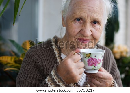 Elderly woman with cup of tea at the balcony - stock photo