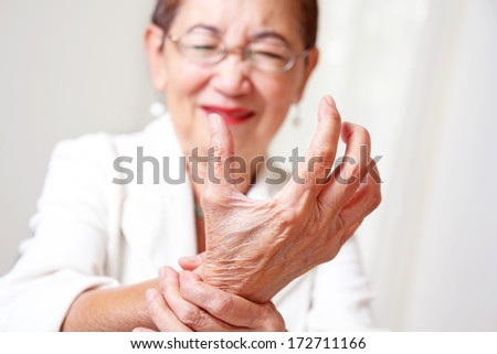 Elderly woman with hand arthritis grimace in pain. - stock photo