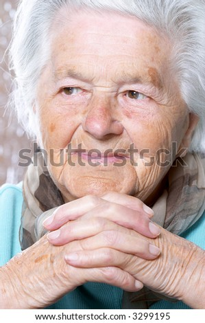 Elderly woman with hands clasped under the chin, looking away - stock photo