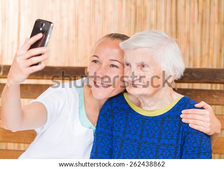 Elderly woman with her caregiver taking a selfie photo - stock photo