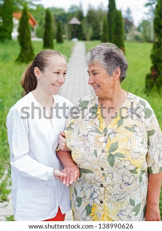 Elderly woman with her caretaker walking in the nature - stock photo