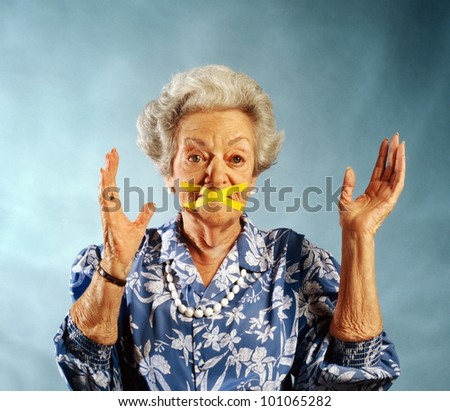 elderly woman with mouth taped closed - stock photo