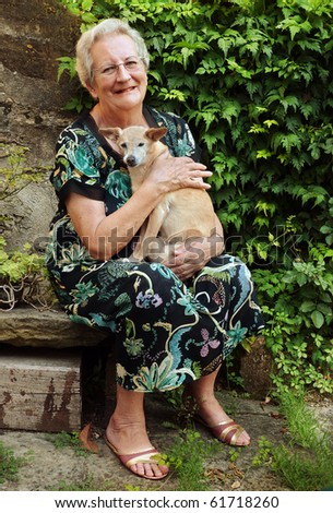Elderly woman with pet dog - stock photo