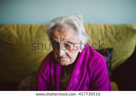 Elderly woman with sad expression at home