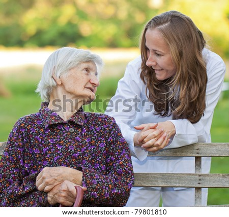 Elderly woman with the young sweet doctor - stock photo