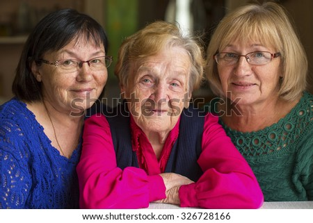 Elderly woman with two adult daughters. - stock photo