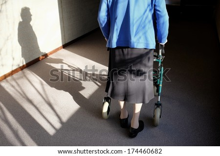 Elderly woman with walker in a hallway, black and white - stock photo