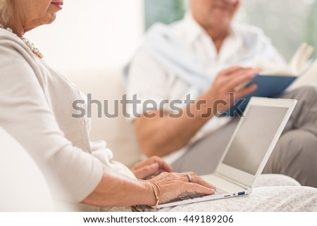 Elderly woman witting on couch and looking at laptop
