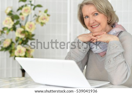 Elderly woman working on laptop computer and smiling