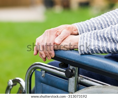 Elderly womans hands resting on a wheelchair