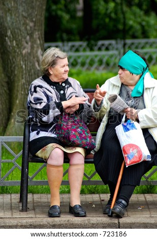 Elderly women talk in park on a bench - stock photo