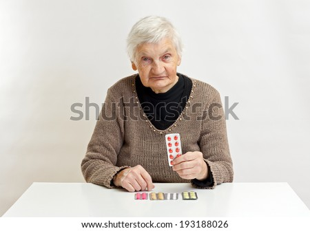 Elderly wrinkled woman holding medicine in her hand - stock photo