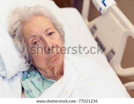 Elderly 80 year old woman with Alzheimer's disease in a hospital bed. - stock photo