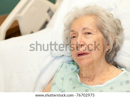 Elderly 80 year old woman with Alzheimer's in a hospital bed. - stock photo