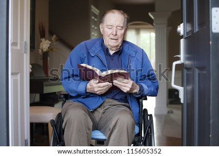 Elderly 90 yr old man in wheelchair at his front door, reading a Bible - stock photo