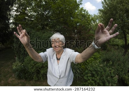 Eldery, gray woman in garden - stock photo