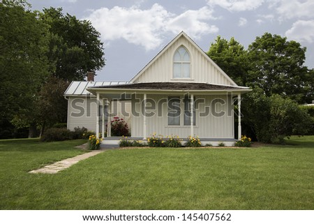 ELDON, IA - JUNE 19: American Gothic House designed in Gothic revival style, known for backdrop of the 1930 painting American Gothic by Grant Wood, on June 19, 2013 in Eldon, Iowa. - stock photo