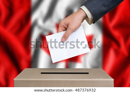 Election in Canada. The hand of man putting his vote in the ballot box. Canadian flag on background.