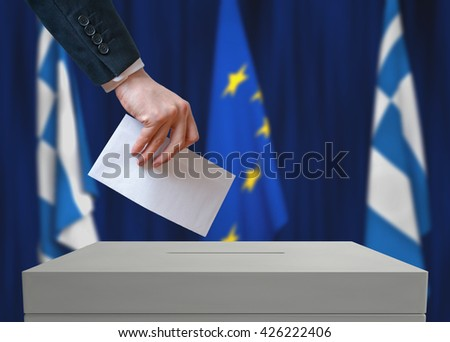 Election in Greece. Voter holds envelope in hand above vote ballot. Greek and European Union flags in background. - stock photo