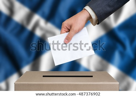 Election in Scotland. The hand of man putting his vote in the ballot box. Scottish flag on background.