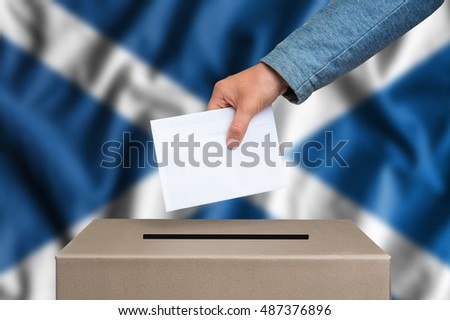 Election in Scotland. The hand of woman putting her vote in the ballot box. Scottish flag on background.