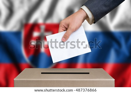 Election in Slovakia. The hand of man putting his vote in the ballot box. Slovak flag on background.