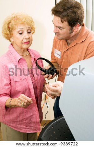 Election volunteer provides headphones to assist a senior woman in voting. - stock photo