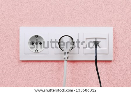 Electric and internet outlets on pink wall, electric cable and internet - stock photo