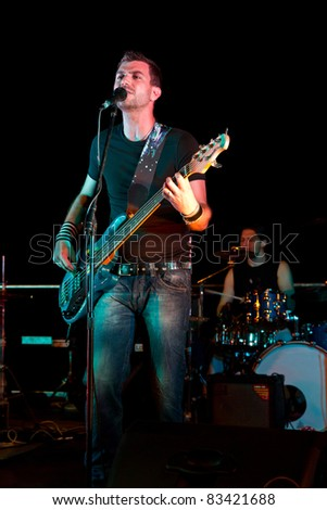 Electric bass-guitar player during a concert - stock photo
