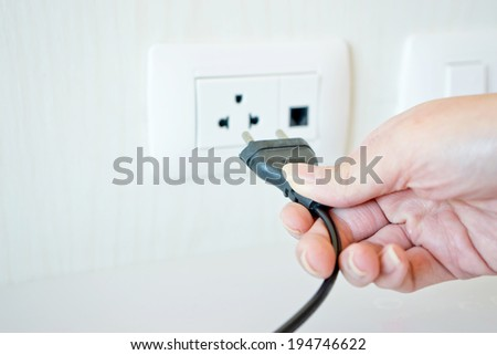 Electric cable with hand and Electrical Outlet on the Wall.  - stock photo