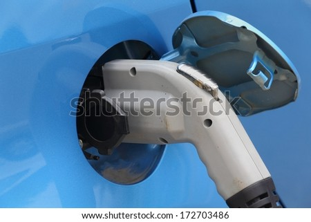 Electric Car Plug Close Up. Close up of the power supply plugged into an electric car being charged.  - stock photo
