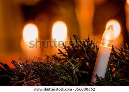 Electric Christmas light on a tree with candlelight in the background - stock photo