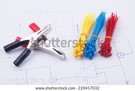 Electric clamps and plastic ties on a background of the electric scheme